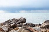 Rotsen en regen op zee. — Stockfoto