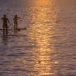 Stock Photo: Two paddlesurfers intertwined.