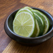 Stock Photo: Slices of lime in small brown bowl