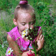 Happy little girl in grass smelling daisies — Stock Photo