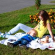 Mother and her baby sitting on the grass — Stock Photo