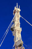 Telecommunications mast on a blue background — ストック写真