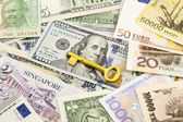 Golden key  and world currency money banknotes  — Stock Photo