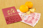 Chinese new year with money yuan banknote and ingot — Stock Photo