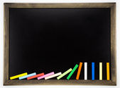 Blank blackboard with domino colorful chalks — Stock Photo