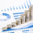 Stacks of coins on graphs and charts — Stock Photo #50157099