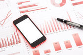 Blank mobile phone  on red graphs, charts , data and business re — Stock Photo