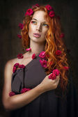 Red-haired girl in flowers — Stock Photo