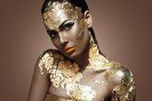 Beautiful woman and gold. — Stock Photo