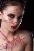 Girl in a web of threads. — Stock Photo