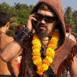 An unidentified man in a necklace of flowers and sun glasses talking on the phone at the annual festival of Freaks, Arambol beach, Goa, India, February 5, 2013. — Stock Photo #29877143