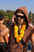 An unidentified man in a necklace of flowers and sun glasses talking on the phone at the annual festival of Freaks, Arambol beach, Goa, India, February 5, 2013. — Stock Photo