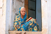 16.10.2012 - Jaisalmer. Rajasthan, India. Elderly woman reading a book on his doorstep. — Stock Photo