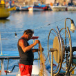 Fisher in a boat fixing his net in Ayia Napa — Stock Photo
