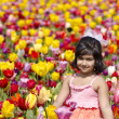 A cute girl in a tulip garden — Stock Photo