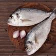 Stock Photo: Two fresh sebream on chopping board, top view.
