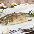 Two grilled trouts with fresh herbs and lemon pieces on wooden t — Stock Photo