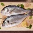Raw fish with ingredients on wooden chopping board. — Stock Photo