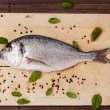 Fish on wooden board with herbs and spices. — Stock Photo