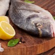 Delicious fish sea bream on wooden cutting board. — Stock Photo