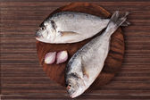 Fish on wooden chopping board. — Stock Photo