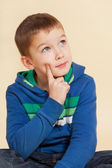 Young cute boy sitting and thinking. — Stock Photo