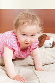 Cute baby girl looking into camera on bed. — Stock Photo