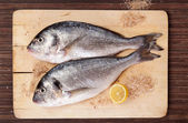 Two fish on wooding kitchen board. — Stock Photo