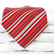 Pile of white shirts with red tie. — Stock Photo