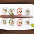 Maki sushi on white plate with chopsticks. — Stock Photo