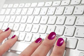 Close-up of female hand touching a white metal keyboard. — Stock Photo