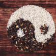 Black and white rice forming a yin yang symbol — Stock Photo