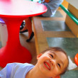Little girl and red table — Stock Photo