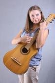 Hermosa chica de ojos azules, tocando la guitarra sobre fondo gris — Foto de Stock