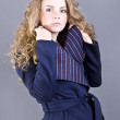 Beautiful curly blonde with a languid sight in the blue coat on gray background — Stok fotoğraf