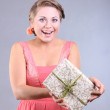 Beautiful young happy girl with blue eyes holding gift boxes on gray background — 图库照片