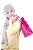 Pretty young blonde in a gray cap and a gray scarf with pink gift bag in hand on white background — Stock Photo