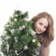Beautiful smiling blond girl with Christmas tree dressed up in her arms on a white background — Stock Photo #36526135