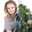 Beautiful smiling blond girl with Christmas tree dressed up in her arms on a white background — Stock Photo #36526203