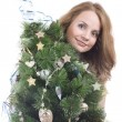 Beautiful smiling blond girl with Christmas tree dressed up in her arms on a white background — Stock Photo #36526261