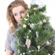 Beautiful smiling blond girl with Christmas tree dressed up in her arms on a white background — Stock Photo #36526281