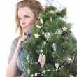 Beautiful smiling blond girl with Christmas tree dressed up in her arms on a white background — Stock Photo #36526285