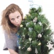 Beautiful smiling blond girl with Christmas tree dressed up in her arms on a white background — Stock Photo #36526989