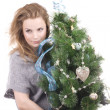 Beautiful smiling blond girl with Christmas tree dressed up in her arms on a white background — Stock Photo #36527027