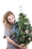 Beautiful smiling blond girl with Christmas tree dressed up in her arms on a white background — Stock Photo