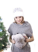 Pretty girl in hat near Christmas tree Snow Maiden with a gray teddy bear in her arms on a white background — Stockfoto