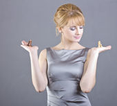 Beautiful young girl holding chess pieces in hand on gray background — Stock Photo