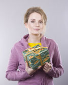 Beautiful young woman holding a bright gifts on gray background — Stock Photo