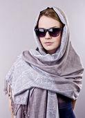 Güzel bir genç kadın bir gri şal ve gri arka plan üzerinde gözlük işlemeli — Stok fotoğraf