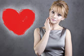 Beautiful young blond woman on the background near gray wall with a bright red heart — Foto Stock